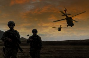 Two soldiers walking in the battlefield while two military helicopter flying over them during a military operation at sunset.
